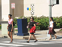 Three female pedestrians crossing a street.